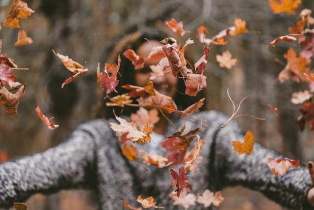 落ち葉を投げる女性の画像